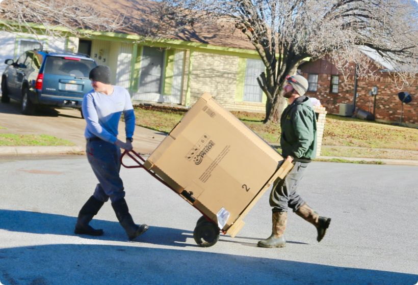 Technicians Carrying a Cardboard Box